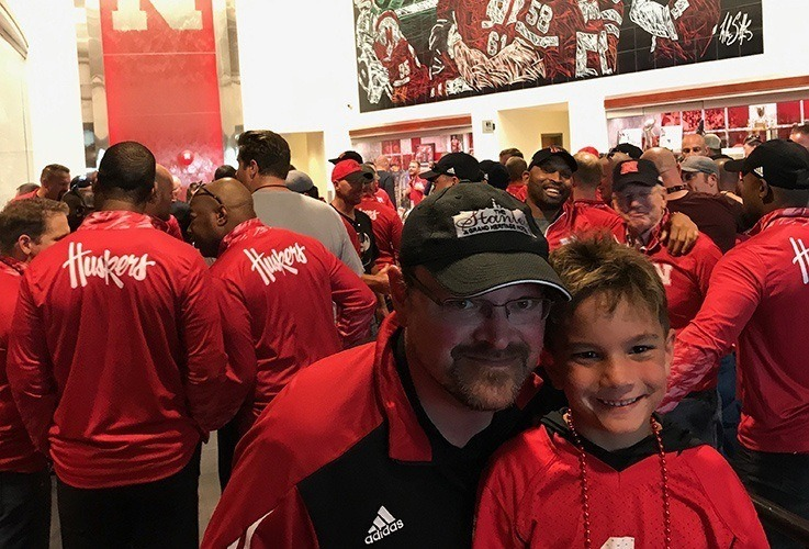 Dr. Gessford and son posing with Nebraska con huskers