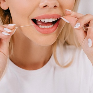 An up-close view of a female using dental floss to remove an object from between her teeth