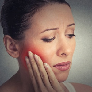 A woman holding the side of her face in pain because of a partially dislodged tooth