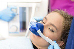 Girl with nitrous oxide mask in dental chair