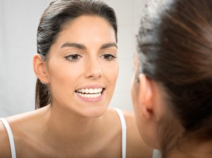 Woman looking at her brilliant smile in the mirror after teeth whitening in Lincoln
