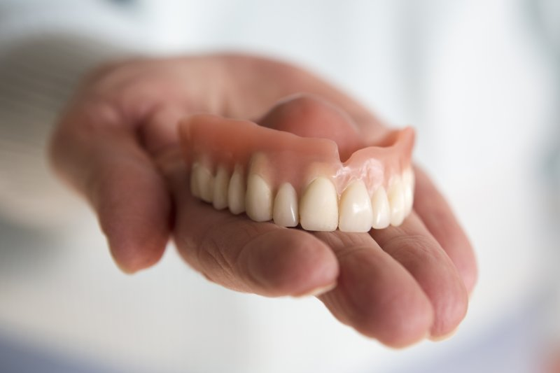 a person holding a top full denture in their hand