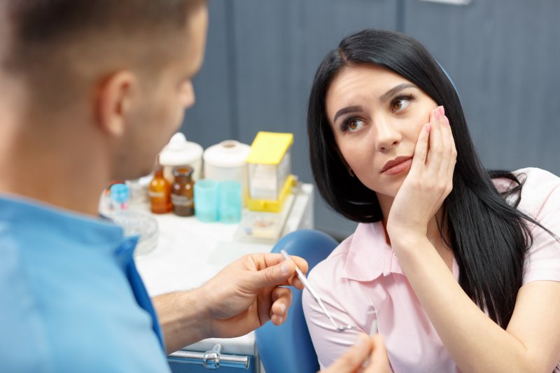 a young woman with dark hair holding her cheek as she listens to her dentist explain that she needs a root canal