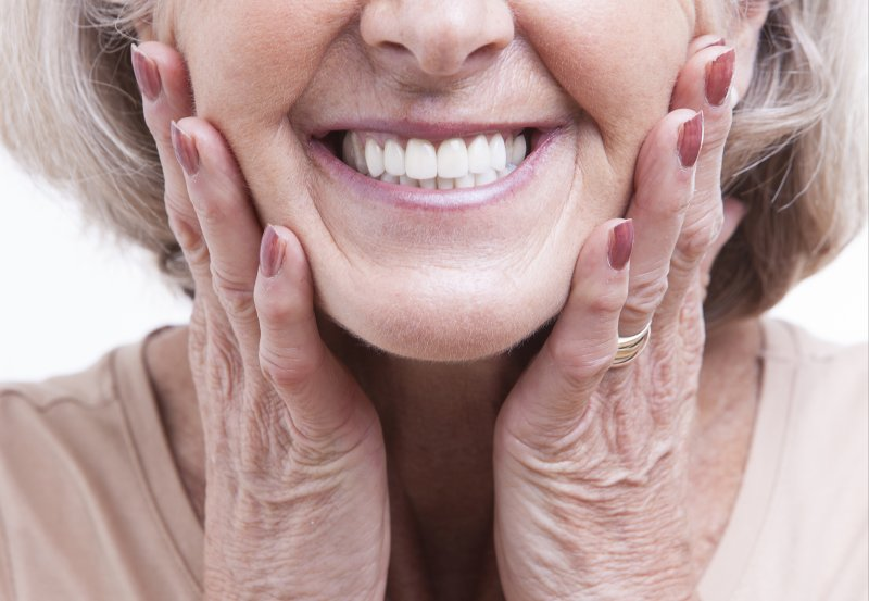an up-close image of an older woman holding both sides of her face and smiling to show off her dentures