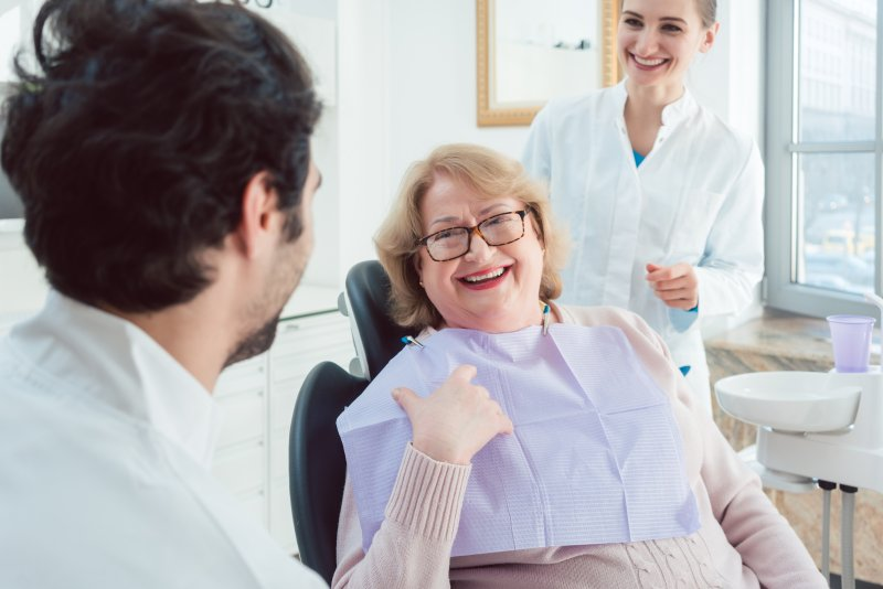 an older woman smiling while talking to her dentist and dental hygienist