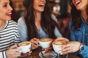 women smiling and drinking coffee