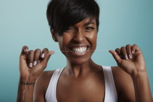 woman flossing her teeth to get rid of gingivitis in Lincoln