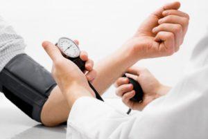 dentist taking a patient's blood pressure